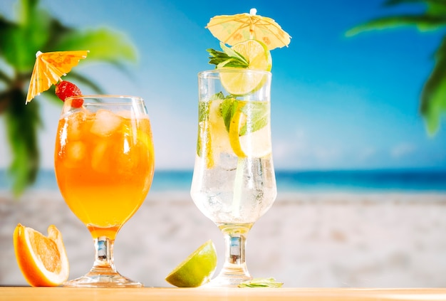 Festively decorated glasses with strawberry orange drink and sliced lime