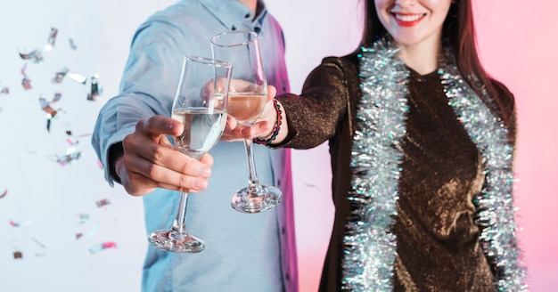 Festively dressed couple clinking champagne glasses