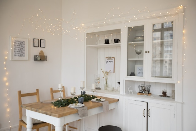 Festively laid white table and chairs in living room