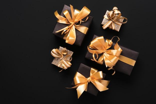 Празднично завернутые золотые подарочные коробки на черном фоне. плоский стиль. концепция праздника и черной пятницы.