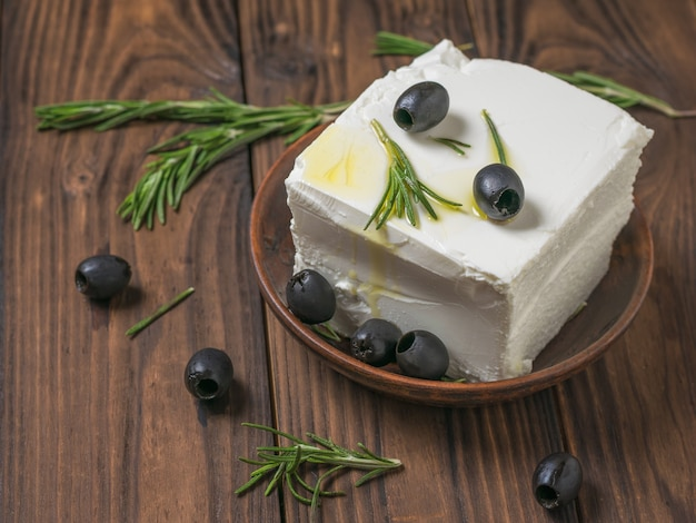 Feta cheese in a clay bowl with olives on a wooden table. natural cheese made from sheep's milk.