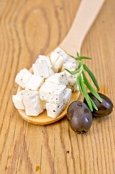 木のスプーンのフェタチーズ、木の板の背景にブラックオリーブとローズマリー