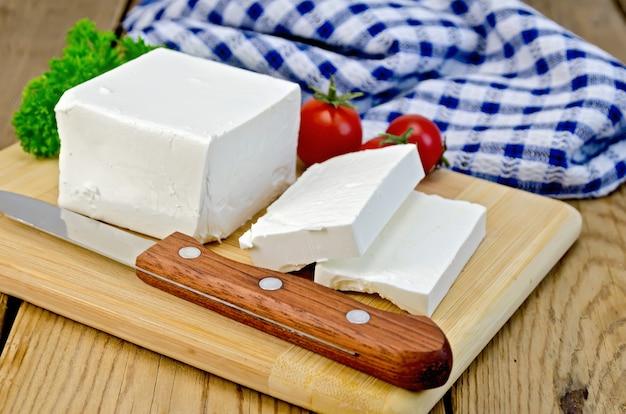 フェタチーズ、ナイフ、パセリ、トマト、木の板にナプキン