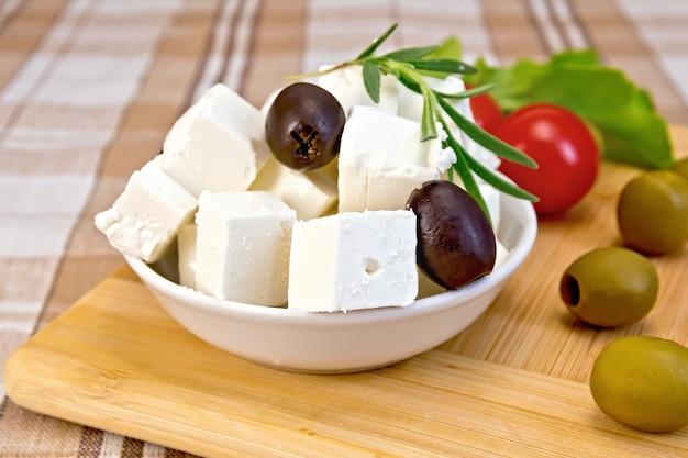 白いボウルにフェタチーズ、オリーブ、ローズマリー、茶色の生地