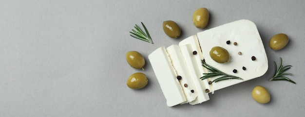Feta cheese, olives, rosemary and pepper on gray
