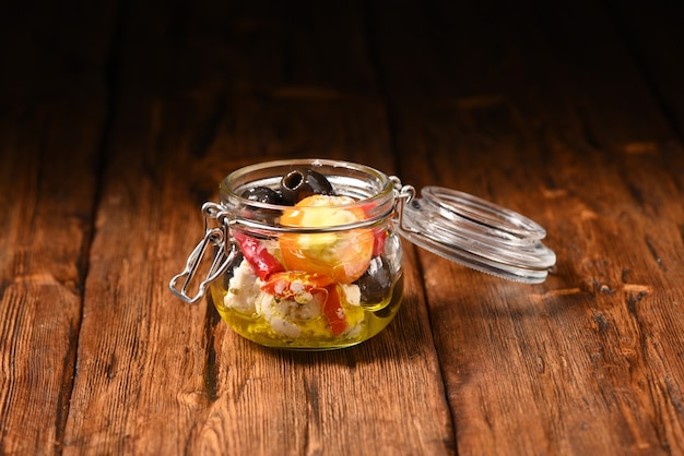 Маринованный перец и оливки с сыром фета в банке для хранения на деревянном столе