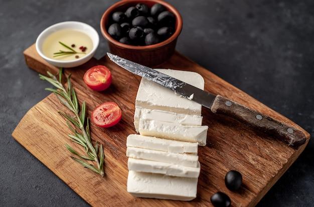 Сыр фета, с розмарином, помидорами, оливками на каменном фоне.