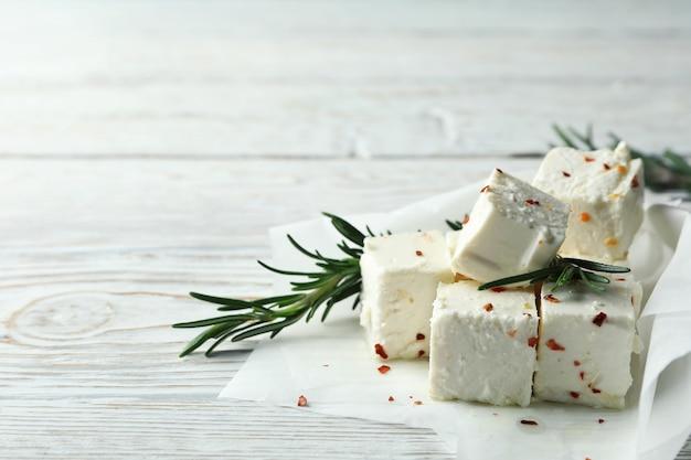 Сыр фета со специями и розмарином на белом деревянном