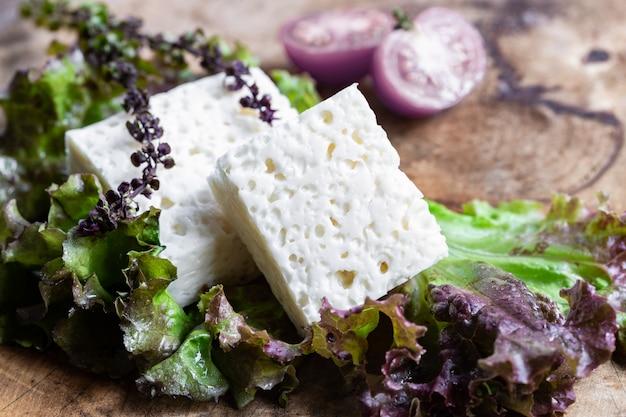 Козий сыр фета с зеленым салатом на деревенском деревянном
