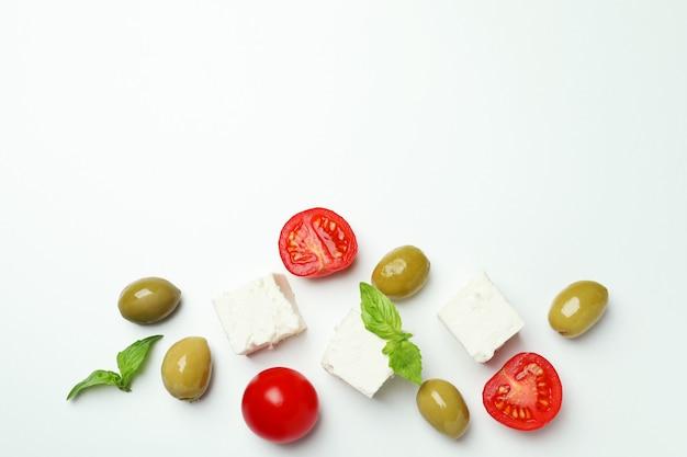 白い表面にフェタチーズ、オリーブ、トマト、バジル