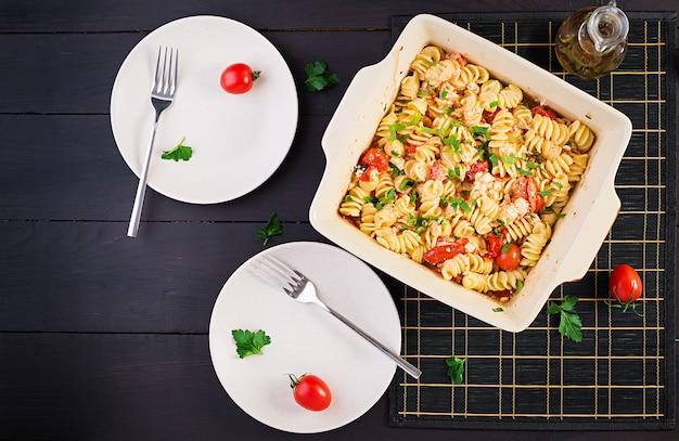 フェタパスタ。チェリートマト、フェタチーズ、ニンニク、ハーブで作られたトレンドのフェタチーズ焼きパスタレシピ。テーブルセッティング。上面図、上の、コピースペース。
