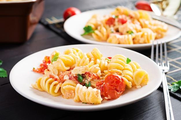 페타 파스타. 체리 토마토, 페타 치즈, 마늘 및 허브로 만든 트렌드 페타 베이크 파스타 레시피. 테이블 세팅.