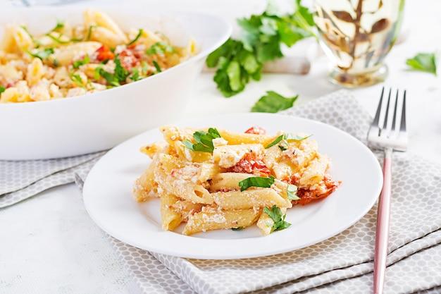 フェタパスタ。チェリートマト、フェタチーズ、ニンニク、ハーブで作られたトレンドのフェタチーズ焼きパスタレシピ。