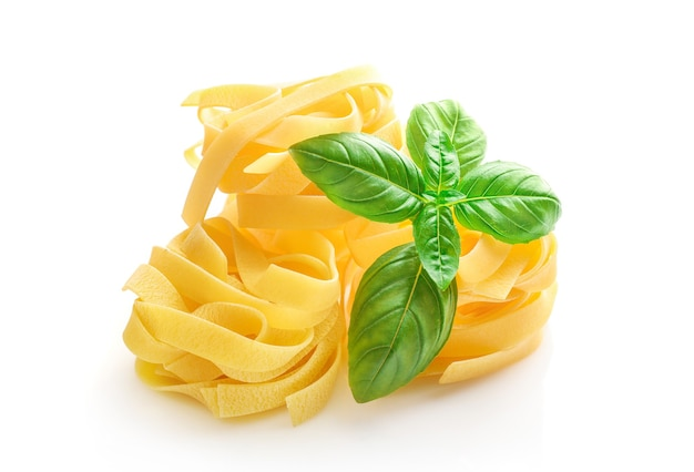 Fettuccine italian pasta and basil leaves isolated on white.