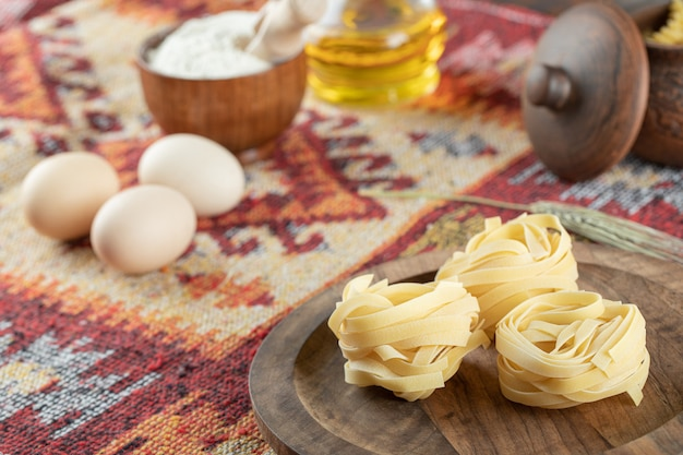 Fettuccine italian pasta on wooden board with eggs and flour