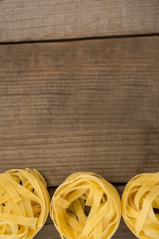 Fettuccine pasta arranged in a row on wooden background