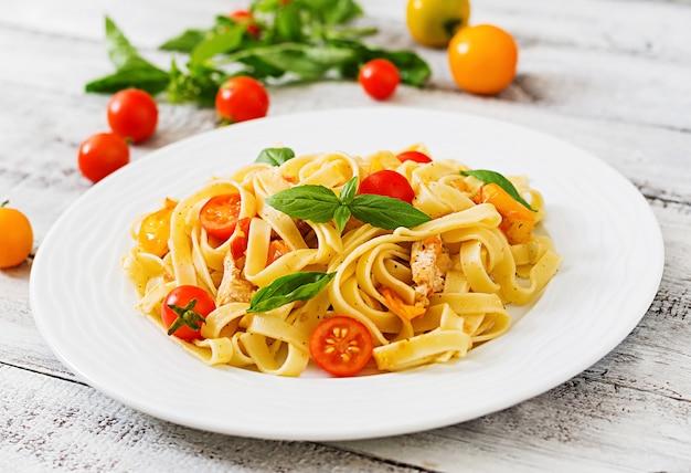 Феттучини паста в томатном соусе с курицей, помидоры украшенные базиликом стол