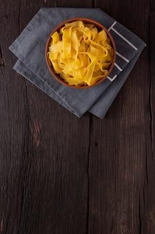 Паста феттучини на деревянном столе в миске. вид сверху. вегетарианская пища.