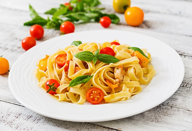 Fettuccine pasta in tomato sauce with chicken, tomatoes decorated with basil  table