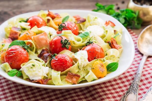 구운 토마토, 베이컨, 소박한 나무 배경에 모짜렐라 치즈와 페투치니 파스타. 선택적 초점.
