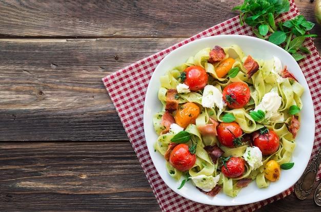 구운 토마토, 베이컨, 소박한 나무 배경에 모짜렐라 치즈와 페투치니 파스타. 평면도.