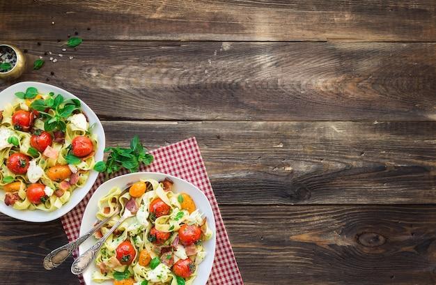 소박한 나무 배경에 구운 토마토 베이컨과 모짜렐라 치즈를 곁들인 페투치니 파스타