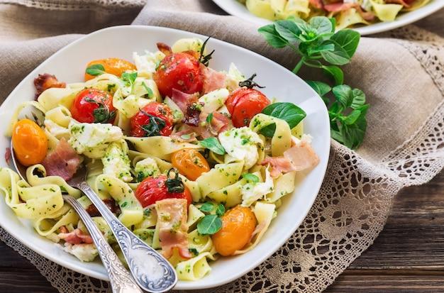 소박한 나무 표면에 구운 토마토, 베이컨, 모짜렐라 치즈와 페투치니 파스타. 선택적 초점.
