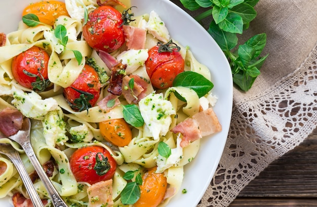 소박한 나무 표면 상위 뷰에 구운 토마토 베이컨과 모짜렐라 치즈와 페투치니 파스타