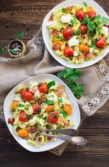소박한 나무 표면 상위 뷰에 구운 토마토 베이컨과 모짜렐라 치즈와 페투치니 파스타 프리미엄 사진
