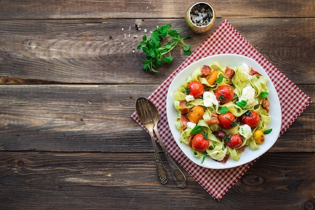 Fettuccine pasta with baked tomatoes bacon and mozzarella cheese on rustic wooden background