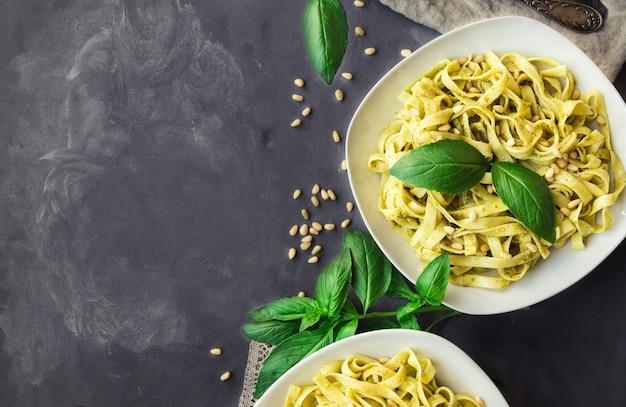 콘크리트 배경 이탈리아 요리에 페스토 소스 바질과 잣을 곁들인 페투치니 파스타