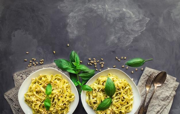 Паста феттучини с соусом песто, базиликом и кедровыми орехами на бетоне. итальянская кухня