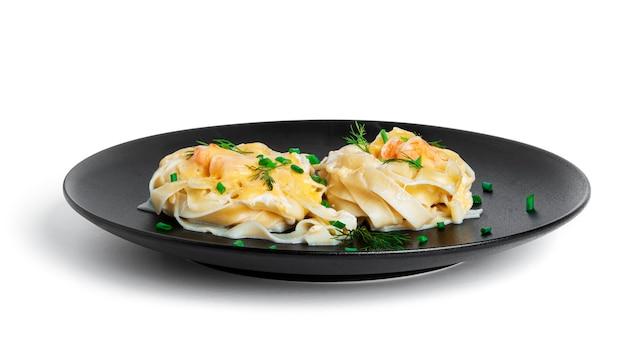 Паста феттучини с креветками в сливочном соусе на черной тарелке, изолированной на белом. гнезда из макарон с морепродуктами и сыром.