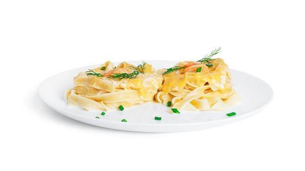 Паста феттучини с креветками в сливочном соусе на белой тарелке, изолированной на белом. гнезда из макарон с морепродуктами и сыром.