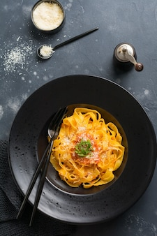 Fettuccine pasta with traditional italian passat sauce and parmesan cheese in light plate on old white concrete background. top view.
