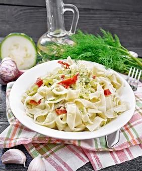 ズッキーニと赤唐辛子のクリーミーソースのフェットチーネパスタ、キッチンタオル、ニンニク、木の板の背景に白いプレートのフォーク