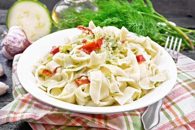Fettuccine pasta with zucchini and hot red pepper in creamy sauce in white plate on a kitchen towel, garlic and a fork on dark wooden board background