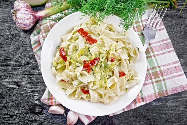 Fettuccine pasta with zucchini and hot red pepper in creamy sauce in white plate on a towel, garlic and a fork on wooden board background from above