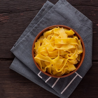 Fettuccine pasta on a wooden table in a bowl. top view. vegetarian food.