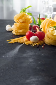 Fettuccine and spaghetti with ingredients for cooking pasta on black stone