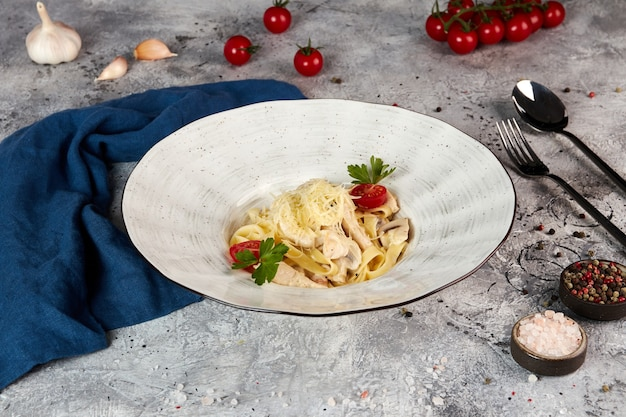 Fettuccine with chicken and mushrooms, gray background