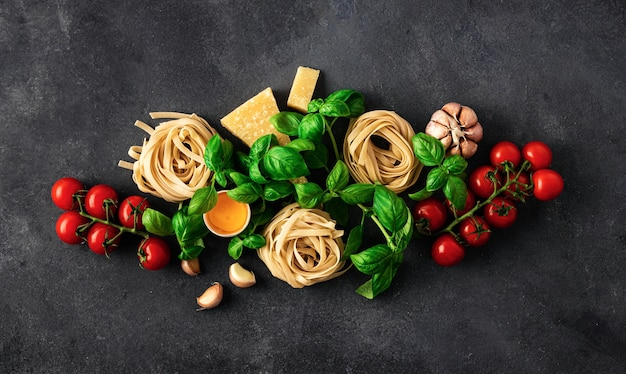 Fettuccine with ingredients for cooking italian pasta on dark