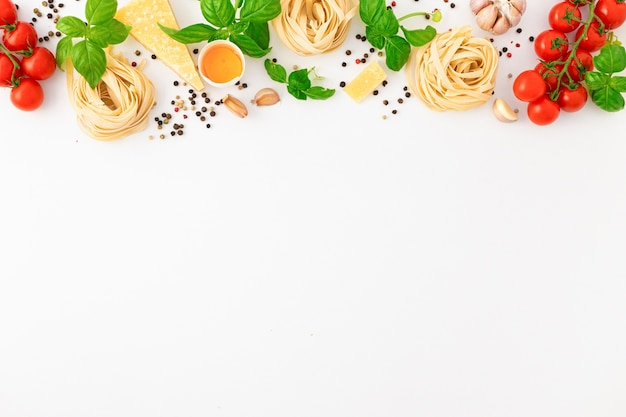 Fettuccine with ingredients for cooking italian pasta on white
