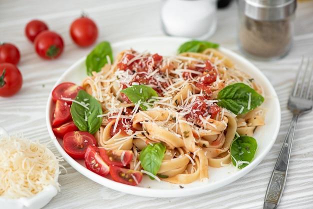 フェットチーネ、トマトソース、パルメザンチーズ、バジルの白い皿の上