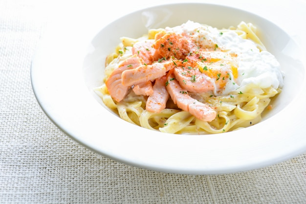 Fettucine with salmon, egg and parmesan cheese, served on white plate.