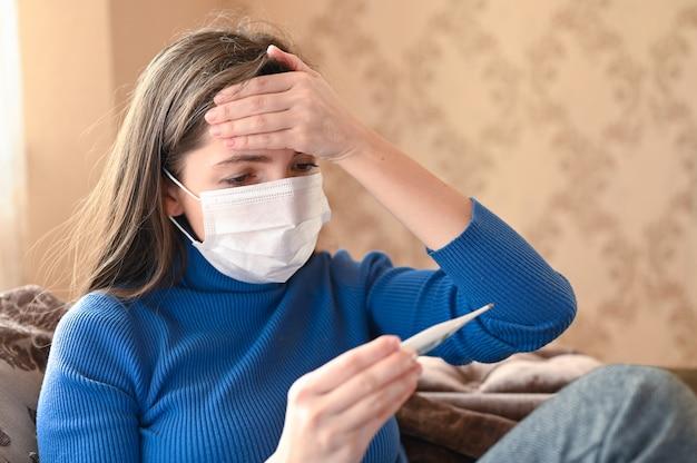 発熱とコロナウイルスの症状、医療用マスクの女性は体温を測定します。閉じる
