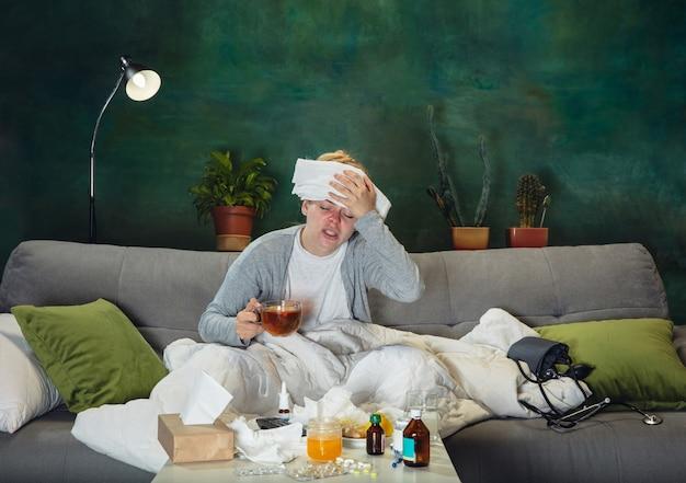 발열과 두통. 열과 감기에 걸린 아픈 어린 소녀는 아프고, 파랗고, 코를 킁킁거리고 있습니다. 고통스럽고 약해 보이며 랩으로 덮습니다. 감기, 바이러스, 계절 그립. 집에서 소파에 앉아 있는 여자.
