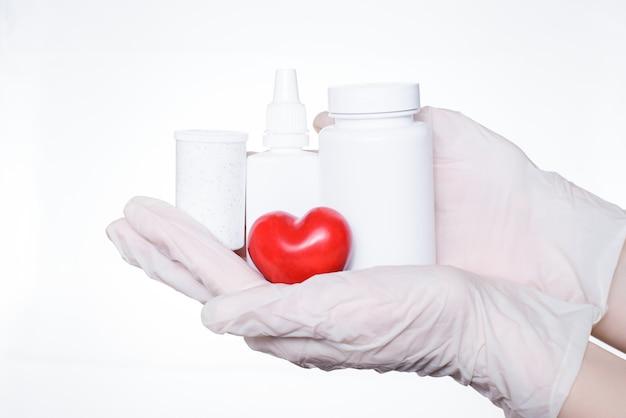 발열 바이러스는 눈의 코 개념을 취합니다. 치료사의 심장 전문의의 손의 사진을 닫습니다 흰색 벽 복사 공간에 고립 약 작은 붉은 마음으로 병 flacon의 표시 보류 세트를 제공합니다