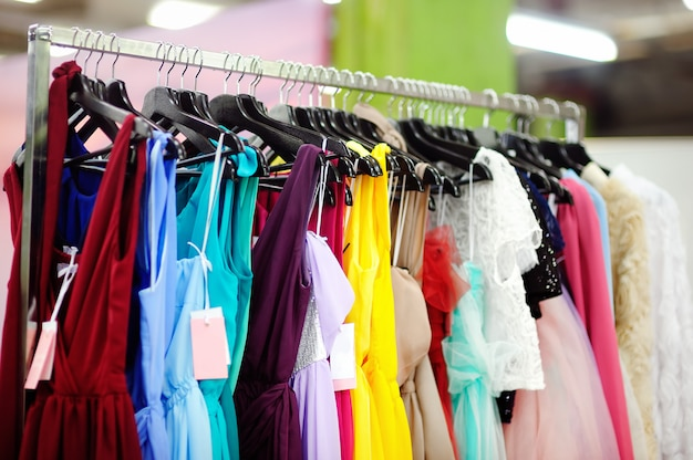 A few beautiful bridesmaid or evening dresses on a hanger in a bridal shop
