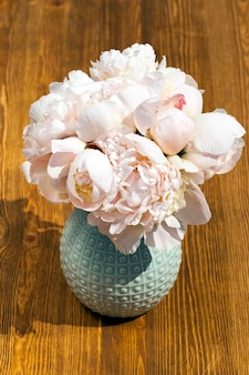 A few beige peony flowers put in a small vase standing on a wooden table. spring season, close-up photo, top view